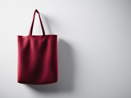 fabric bag: Photo red cotton textile bag hanging left side. Empty white wall background. Highly detailed texture. Stock Photo