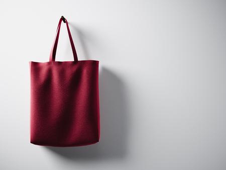 Photo sac de textile en coton rouge suspendu à gauche. Fond de mur blanc vide. Texture très détaillée.