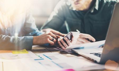 Zakelijke bijeenkomst concept. Photo jonge businessmans crew werken met nieuwe startup project in de moderne loft. Generieke ontwerp smartphone die in vrouwelijke handen. Horizontaal Stockfoto