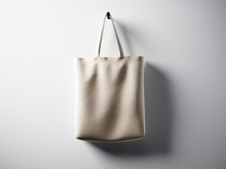 horizontal: Photo natural color cotton textile bag hanging in center. Empty white wall background. Highly detailed texture, space for business message. Stock Photo