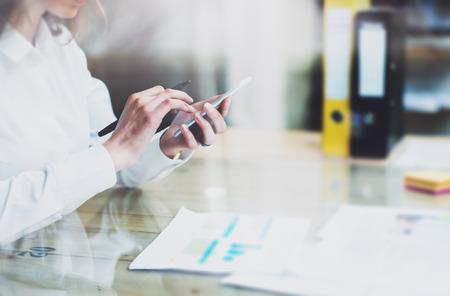 Neue Geschäfts Start. Foto junge Unternehmerin neuen Startprojekt modernen office.Contemporary Smartphone weiblichen Händen halten und berühren screen.Analyze Statistiken plant Tabelle
