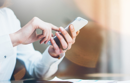 marketing team: Closeup photo businesswoman working new startup project modern office.Contemporary smartphone holding female hands and touching screen