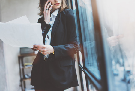 panoramic windows: Young business woman wearing  suit and talking smartphone and holding papers in hands. Open space loft office. Panoramic windows background Stock Photo