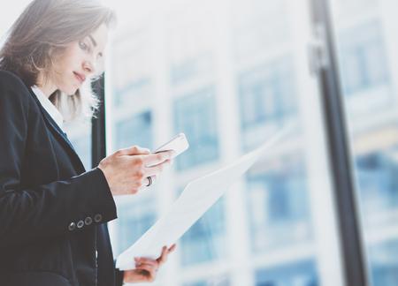 Mujer Pbusiness uso de traje, mirando teléfono inteligente y la celebración de documentos en las manos. Oficina abierta altillo espacio. ventanas panorámicas fondo