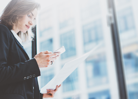 Pbusiness woman wearing suit, looking smartphone and holding documents in hands. Open space loft office. Panoramic windows background Standard-Bild