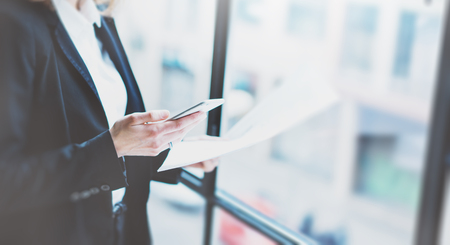 panoramic business: Closeup photo business woman wearing suit, looking smartphone and holding documents in hands. Open space loft office. Panoramic windows background Stock Photo