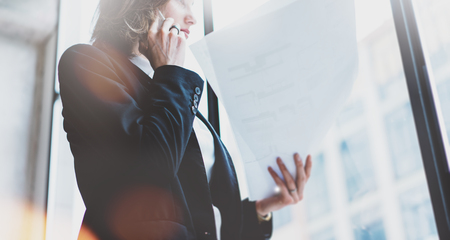 panoramic windows: Business woman wearing white shirt, talking smartphone and holding documents in hands. Loft office. Panoramic windows background