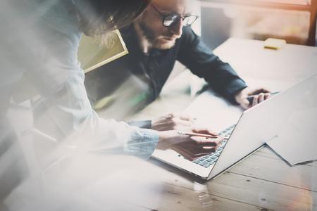 Coworking spotkanie zespołu. Photo młodych businessmans załoga pracuje z nowym projektem startowego w nowoczesnym strychu. Współczesny stół laptop drewna. Zdjęcie Seryjne