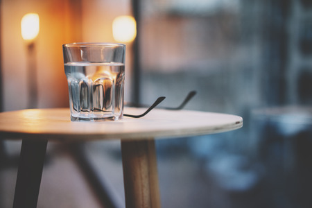 vidrio Photo agua moderno loft mesa de madera interior. Restaurante nadie. Horizontal, fondo borroso, bokeh
