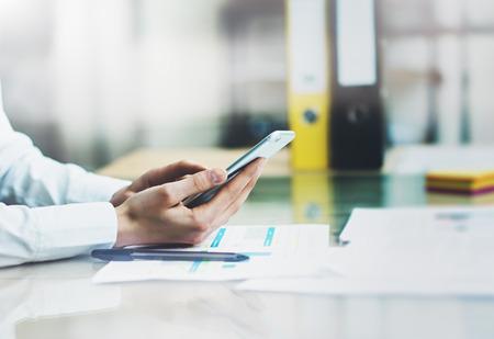 ESTADISTICAS: gerente de cuentas foto del primer trabajo nuevo proyecto de inicio moderno teléfono inteligente office.Contemporary la celebración de las manos femeninas y pantalla táctil. Analizar las estadísticas .Horizontal, efecto de película.