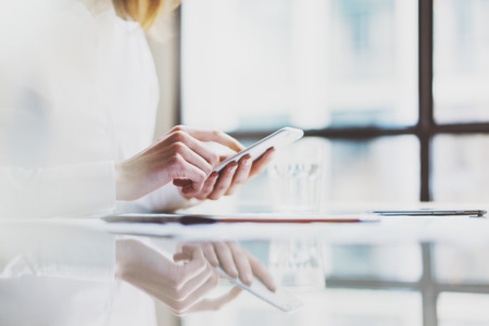 Photo account manager working new startup project modern office.Contemporary smartphone holding female hands and texting message.Glass water.Horizontal, film effect. Blurred windows Stock Photo