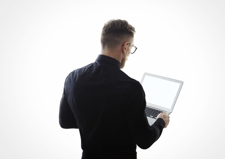 working on laptop: Photo of young businessman wearing black shirt and holding contemporary notebook hands. White empty screen ready for you message. Isolated white background.