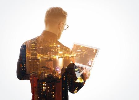 exposicion: Doble exposición joven barbudo hombre de negocios usando la camisa negro y de la mano portátiles contemporáneas. Aislado, fondo de la noche de la ciudad. Foto de archivo