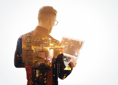 Double exposure  young bearded businessman wearing black shirt and holding contemporary notebook hands. Isolated white, night city background. Imagens