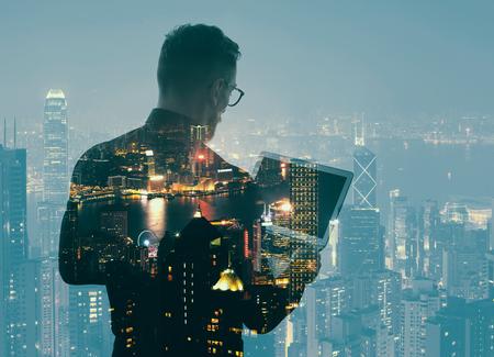 exposicion: Doble exposición joven barbudo hombre de negocios usando la camisa negro y la celebración de las manos modernos portátiles. Vista panorámica noche contemporánea fondo de la ciudad.