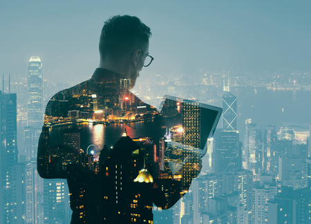 Double exposure young bearded businessman wearing black shirt and holding modern notebook hands. Panoramic view contemporary night city background. Banque d'images