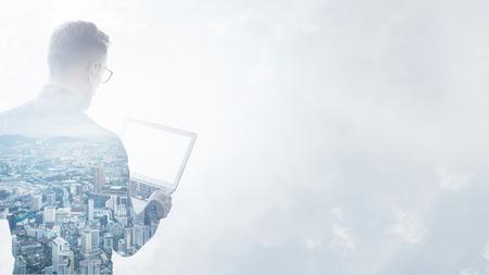 Doppelbelichtung junger bärtiger Geschäftsmann schwarzen Hemd mit zeitgenössischen Notebook trägt hands.Isolated weiß, moderne Stadt background.Blank Bildschirm bereit für Ihr Unternehmen Nachricht.