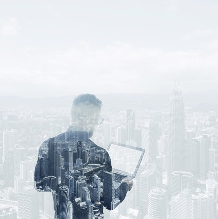 digital background: Double exposure young bearded businessman wearing black shirt holding contemporary notebook.Modern city background.Blank screen ready for your business message.