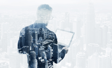 Double exposure young bearded businessman wearing black shirt holding contemporary notebook. Modern megalopolis background. Blank screen ready for your business message. Banque d'images