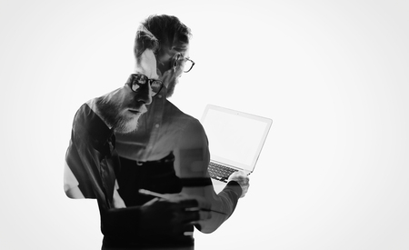 man working computer: Double exposure young bearded businessman wearing black shirt and holding contemporary notebook hands.White empty screen ready for you message.Isolated white,portrait man background.