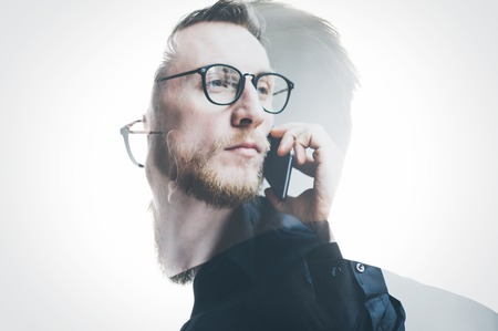exposicion: Doble exposición barba banquero que usa la camisa negro y gafas, sosteniendo la mano contemporánea teléfono inteligente. Aislado, fondo hombre retrato. Foto de archivo