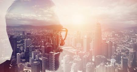 Foto del primo piano di elegante banchiere barba con gli occhiali e guardare città. Doppia esposizione, vista panoramica megalopoli contemporanea sfondo. Spazio per il messaggio di affari.