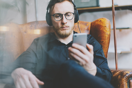 Closeup photo handsome bearded man in headphones listening to music modern loft studio. Man sitting in vintage chair, holding smartphone and relaxing. Panoramic windows background, film effect.