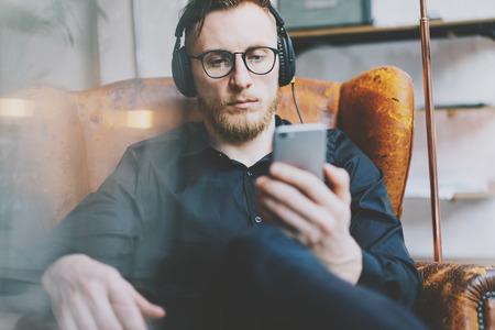 Foto del primer hombre de la barba guapo en los auriculares escuchando música loft moderno. Hombre sentado en la silla de la vendimia, que sostiene teléfono inteligente y relajante. ventanas panorámicas fondo, efectos de película.