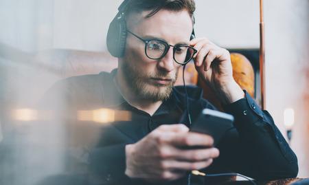 Retrato hermoso hombre con barba auriculares escuchando música moderna studio.Man altillo sentado en la silla de la vendimia, que sostiene teléfono inteligente y relaxing.Horizontal, efecto de película