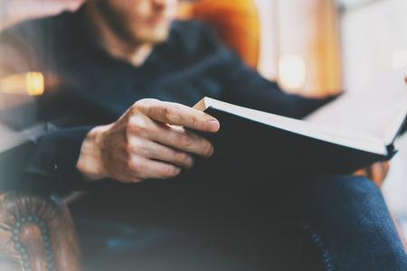 Portret knappe bebaarde man met een bril zwarte shirt.Man zitten in vintage stoel universitaire bibliotheek, het lezen van boeken en te ontspannen. Onscherpe achtergrond. Panoramische ramen, film effect.