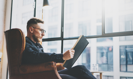Portrait handsome bearded businessman wearing glasses,black shirt.Man sitting in vintage chairmodern loft studio, reading book and relaxing. Blurred background, film effect. Stock Photo
