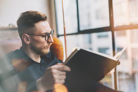 Portret knappe bearded zakenman dragen zwarte shirt. Man zit in vintage chairmodern loft studio, lezen boek en ontspannen. Wazige achtergrond, film effect. Stockfoto