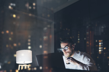 business men: Bearded young businessman working on modern loft office at night. Man using contemporary notebook texting message, holding cup espresso, blurred background, bokeh