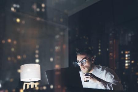 Bebaarde jonge zakenman werken op moderne loft kantoor 's nachts. Man met behulp van moderne notebook texting bericht, houden kopje espresso, vage achtergrond, bokeh