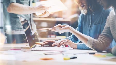 tvůrčí: Úspěch týmu. Foto mladý businessmans posádka pracuje s novým spuštění projektu. Současná notebook na dřevěném stole. Analyzovat plány ruce, klávesnice.