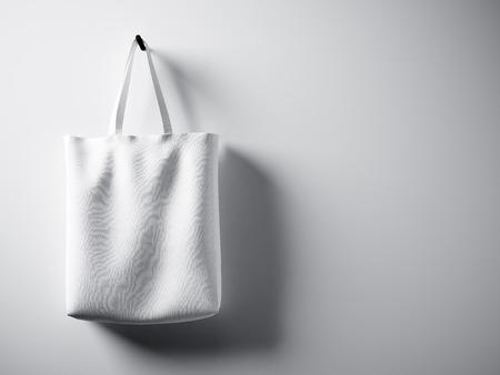 Foto blanca de algodón bolsa de tela colgando del lado izquierdo. Fondo vacío muro de hormigón. Muy detallado, textura.