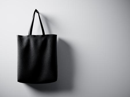 Photo coton noir sac textile pendaison côté gauche. Empty mur blanc fond. texture très détaillée, l'espace pour le message d'affaires.