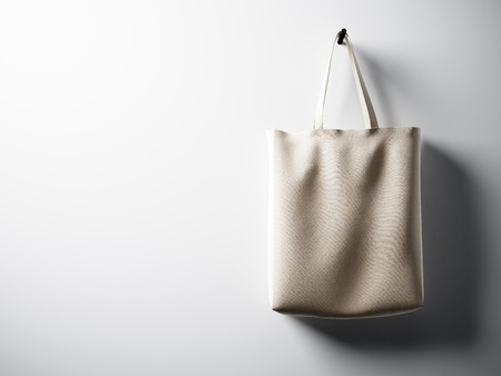 canvas background: Photo black cotton textile bag hanging in right side.  Empty white wall background. Highly detailed texture.