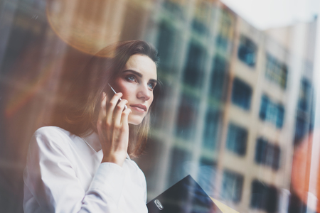 Mujer de negocios Photo llevaba camisa blanca moderna, hablando de teléfonos inteligentes y la celebración de documentos en las manos. Oficina abierta altillo espacio. ventanas panorámicas fondo. maqueta horizontal. Foto de archivo - 54513387