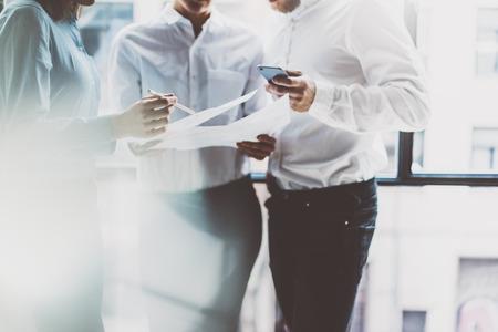 Zespół firmy spotkanie, praca process.Photo profesjonalną załogę pracy z nowymi menedżerami project.Project starcie blisko window.Analyze biznesplanów, smartphone rękach. Niewyraźne tło, efekt filmowy.