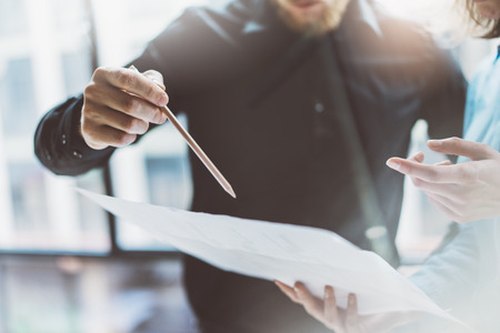 Team job succes.Closeup photo young business managers  working with new startup project in modern office.Analyze document, plans. Holding papers, documents hands. Stock Photo