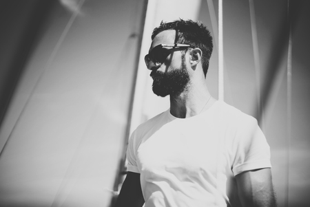 bearded: Portrait of young bearded man standing on the yacht in sunny day. Horizontal Stock Photo