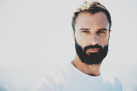 Young bearded guy wearing white blank t-shirt and looking on the camera in sunny day.