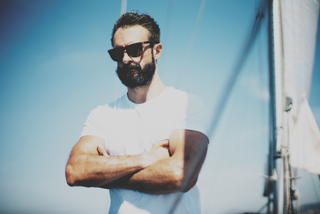 sailing crew: Low angle view of young bearded man standing on the yacht.