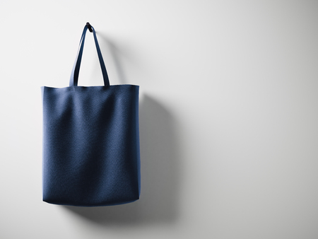 Photo blue cotton textile bag hanging left side. Empty white wall background. Highly detailed texture.