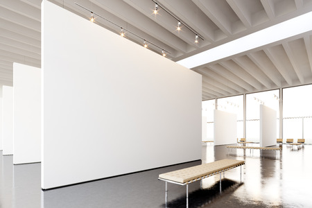 Image exposition modern gallery,open space.Blank white empty canvas hanging contemporary art museum. Interior loft style with concrete floor,light spots and generic design furniture.