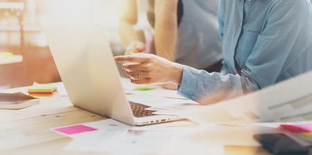 Foto comercialización analizar reunión del equipo. tripulación de negocios joven que trabaja con el nuevo proyecto de inicio en el estudio. Cuaderno moderno en la mesa de madera. Horizontal