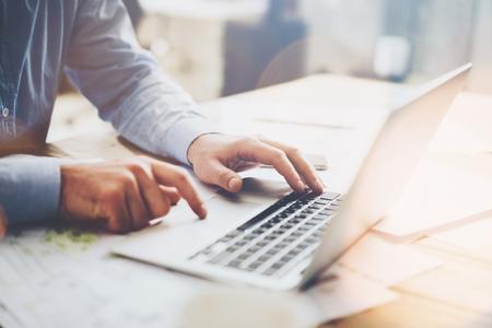 현대 다락방 사무실에서 일하는 사진 사업가. 남자 나무 테이블에 앉아 하 고 현대 노트북, 문자 메시지를 문자 메시지를 사용 하여. 스톡 콘텐츠 - 54558331
