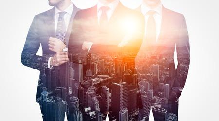 exposicion: Foto del trío de estilo de negocios adulto que desgasta el juego de moda. Doble exposición, vista panorámica al atardecer de fondo de la ciudad contemporánea. mano de obra, el liderazgo, aislado en blanco.