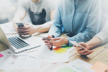 Foto coworking teamvergadering. Jonge zakenman crew werken met nieuwe startup project in de studio. Moderne notebook op houten tafel. Met behulp van moderne smartphones, sms-bericht. Horizontaal